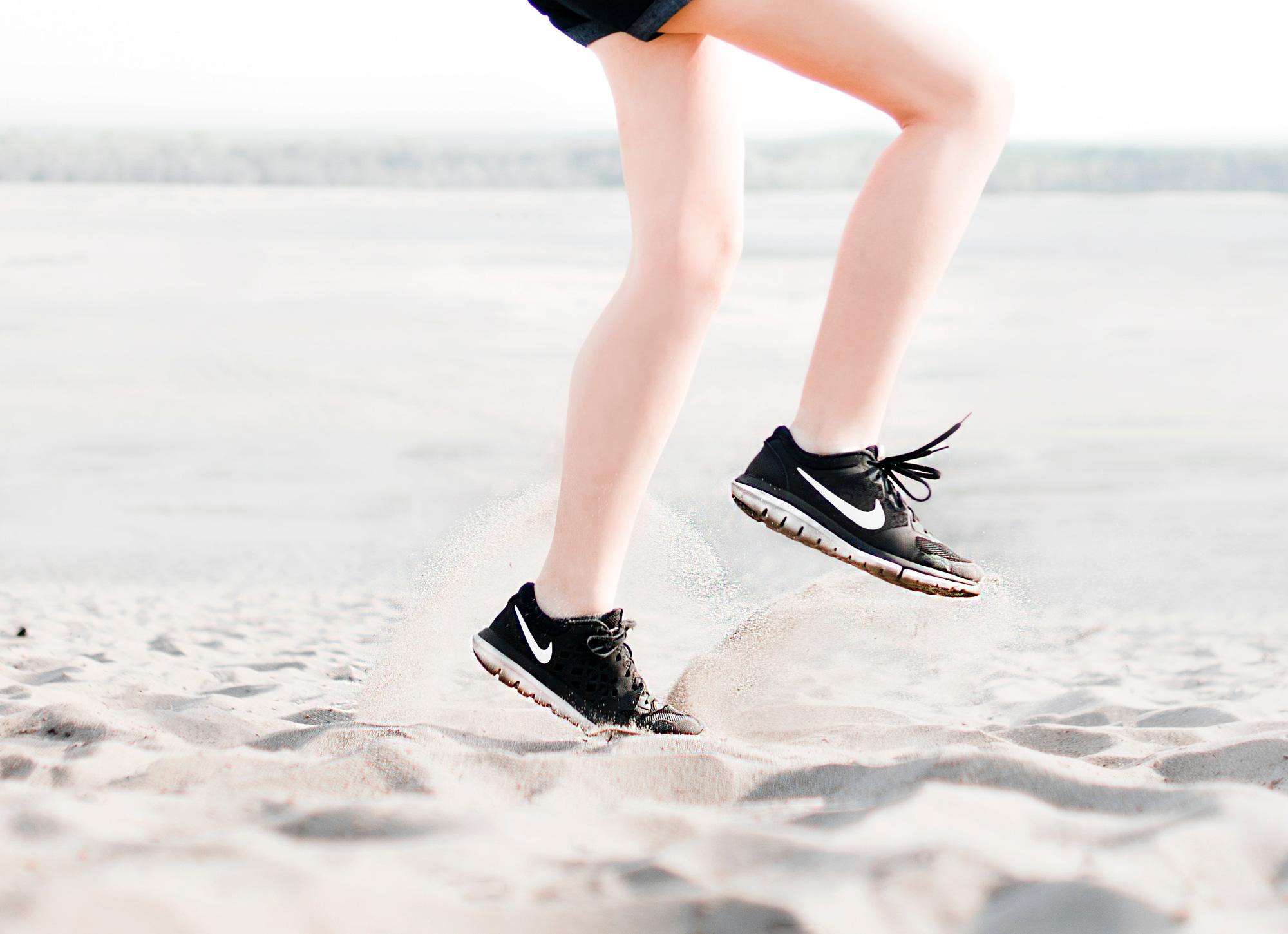 photo-of-woman-wearing-pair-of-black-nike-running-shoes-1166868